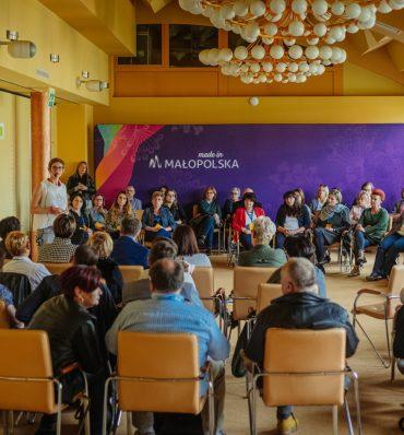 sala wypełniona ludźmi siedzącymi na krzesłach - przy ścianie widać fioletową, dużą grafikę z logotypem Małopolska