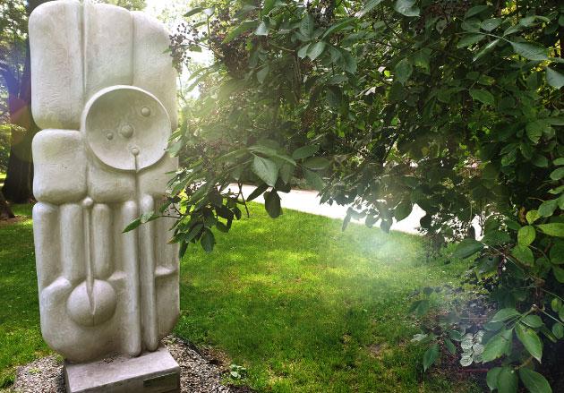 ciekawa rzeźba, wtle zieleń trawy idrzew