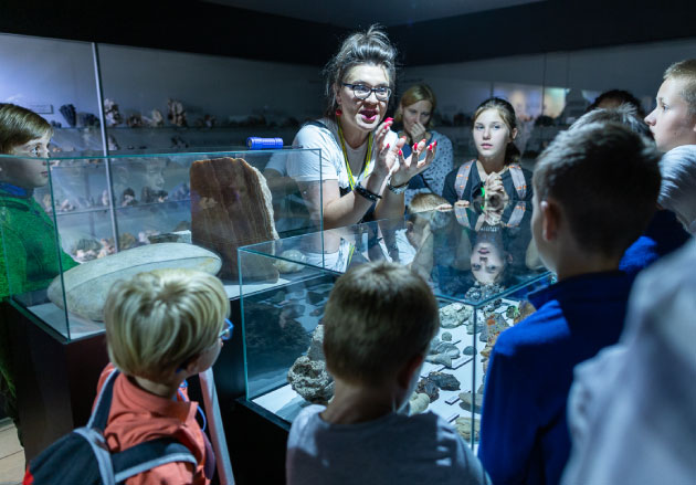 Dzieci słuchające uważnie pani oprowadzącej pomuzeum pośród gablotek zeksponatami