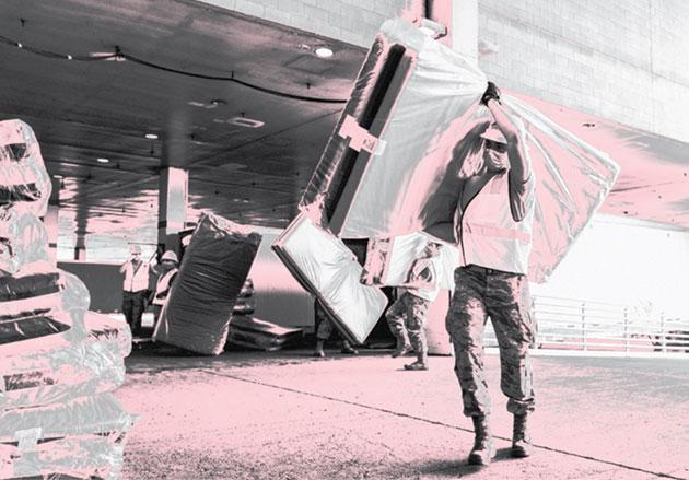 zdjęcie ludzi w maseczkach przenoszących materace