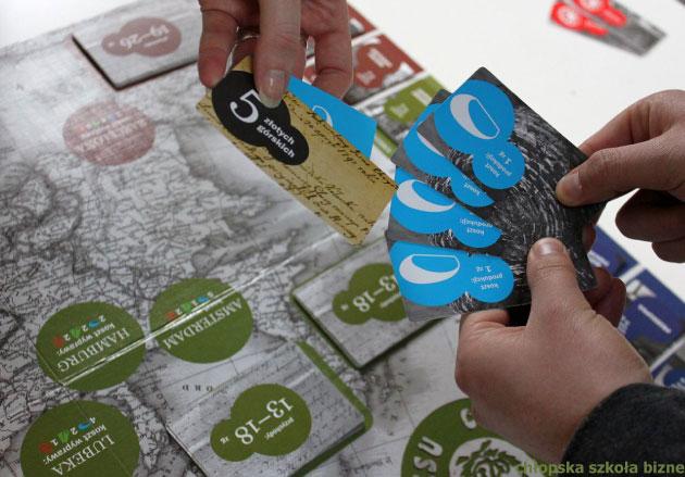 ręce trzymające kilka kart nadplanszą