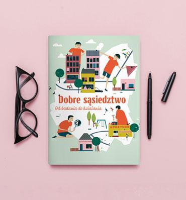 książka z okładką bogatą w kolorowe ilustracje, obok złożone okulary i długopis