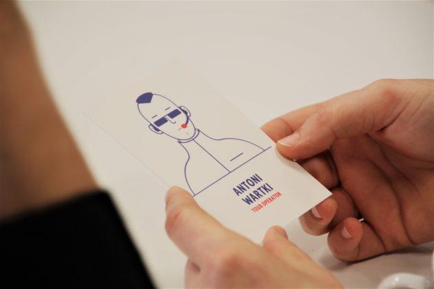 ręce trzymające jedną zkart postaci gry Hamernia - Antoni Wartki, tour operator