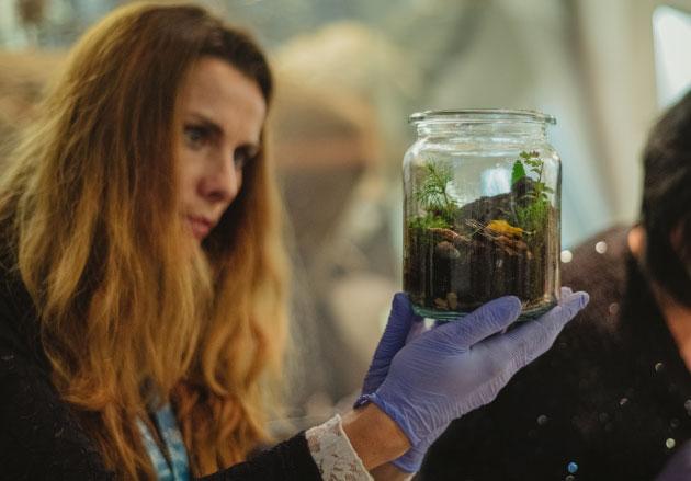 kobieta przyglądająca się słoikowi zziemią iroślinami