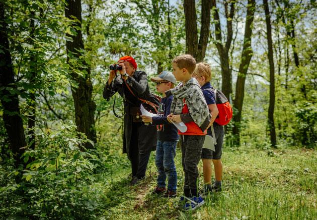 troje dzieci iwypatrująca celu przezlornetkę przewodniczka leśnym wotoczeniu