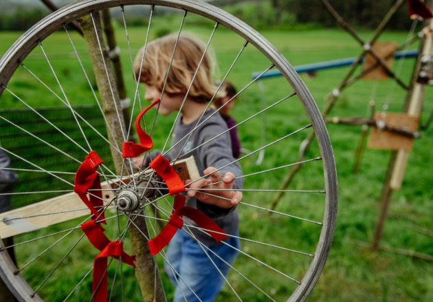 dziecko trzymające wielkie koło zaszprychy