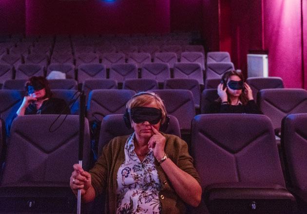 kobieta siedząca nasali kinowej zzasłoniętymi oczami