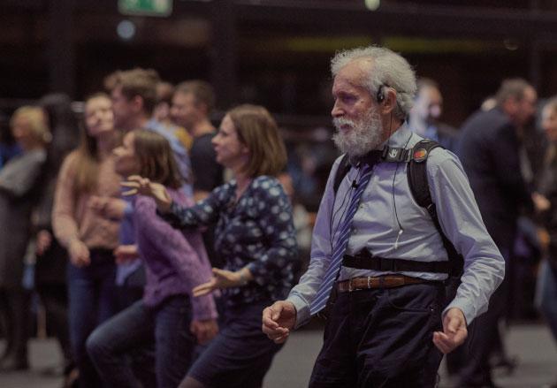 starszy mężczyzna zpętlą indukcyjną wuchu tańczący nakoncercie