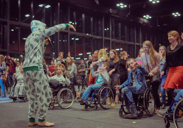lider November Project tańczy iśpiewa blisko publiczności nawózkach inwalidzkich