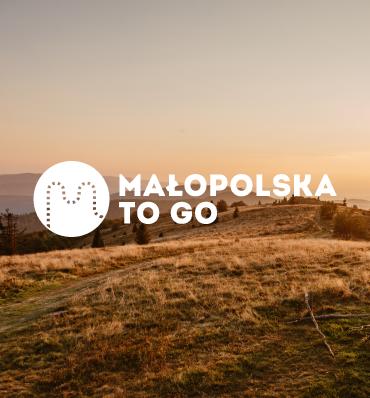logo Małopolska To Go na tle ładnego krajobrazu górskiego z zachodem słońca